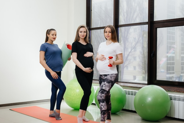 Een groep jonge zwangere meisjes doet yoga en praat binnen. gezonde levensstijl