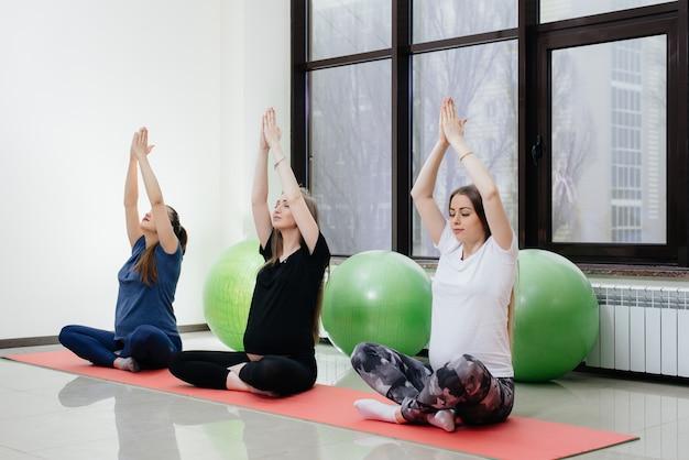 Een groep jonge zwangere meisjes doet yoga en sport op binnenmatten. gezonde levensstijl