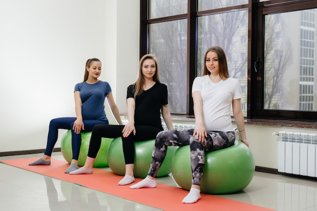 Een groep jonge zwangere moeders houdt zich bezig met pilates en balsporten in een fitnessclub. zwanger