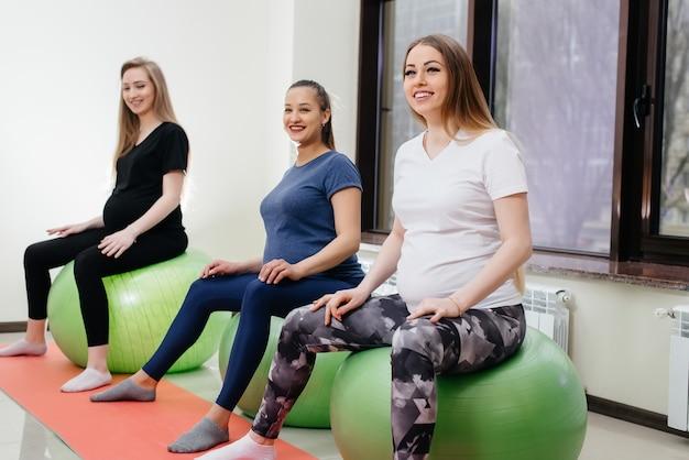 Een groep jonge zwangere moeders houdt zich bezig met pilates en balsporten in een fitnessclub.