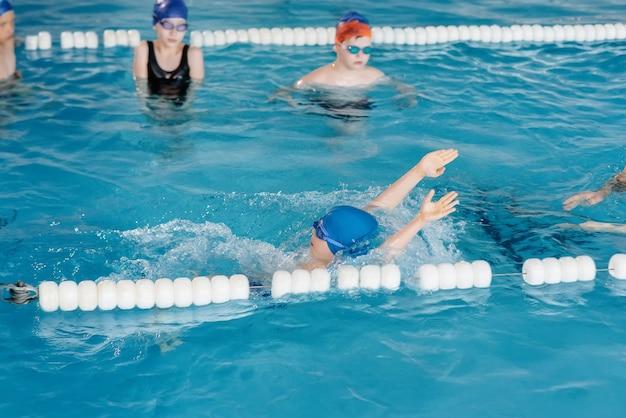 Een groep jongens en meisjes trainen en leren zwemmen in het zwembad met een instructeur. ontwikkeling van kindersporten.