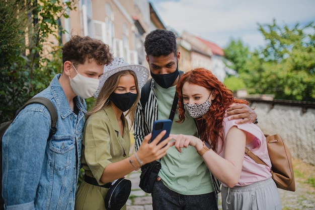 Een groep jongeren buiten op reisstad die selfie neemt met het coronavirus-concept van de smartphone