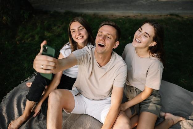 Een groep jongeren die selfies maken in de natuur in het park