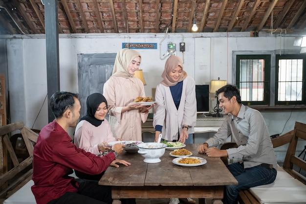 Een groep jongeren komt samen en eet samen in de eetkamer