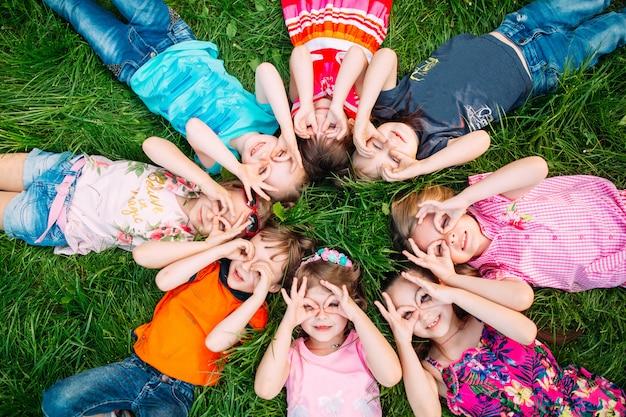Een groep kinderen die op het groene gras in het park liggen. de interactie van de kinderen.