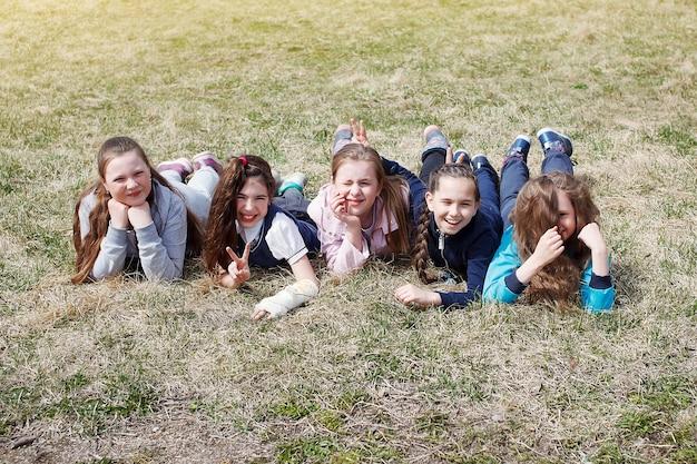 Een groep kinderen lacht, heeft plezier, ligt op een groen gazon. het concept van vrije tijd voor kinderen, een gezonde levensstijl.