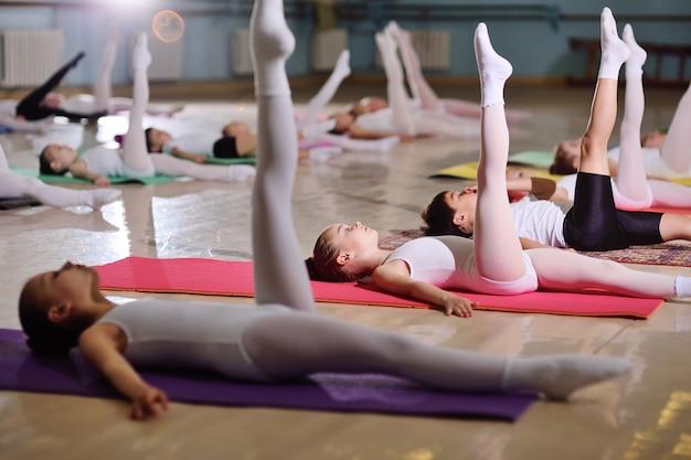Een groep kinderen op een balletschool of in een gymnastiekafdeling over carimat