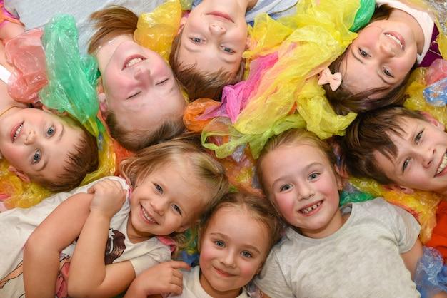 Een groep kinderen op een feest liggend op gekleurd papier en lachen, bovenaanzicht