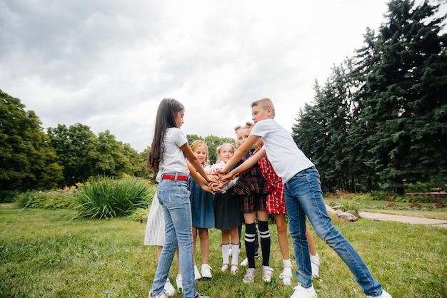 Een groep kinderen rent rond, heeft plezier en speelt als groter team in de zomer in het park. gelukkige jeugd.