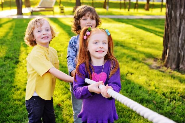 Een groep kleine kleuters speelt een touwtrekwedstrijd in het park.