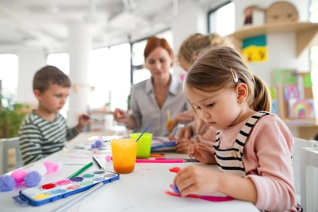 Een groep kleine kleuterschoolkinderen met leraar binnenshuis in klaslokaal, schilderend.