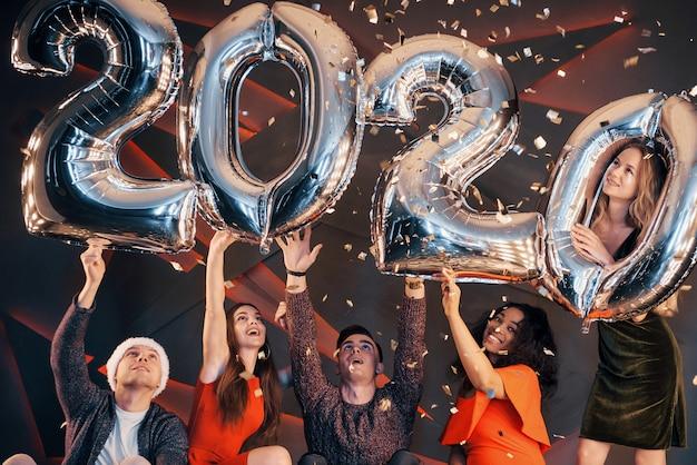 Een groep leuke jonge mooie multinationale mensen die confetti gooien op een feestje. gelukkig nieuwjaar.