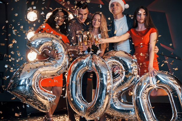 Een groep leuke jonge mooie multinationale mensen die confetti gooien op een feestje. viering van 2020.