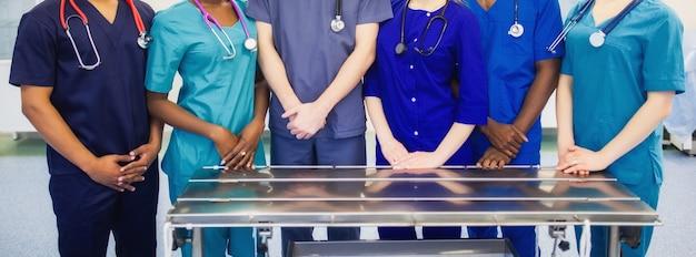 Een groep medische studenten van gemengd ras in chirurgische pakken lacht op de achtergrond van de operatiekamer