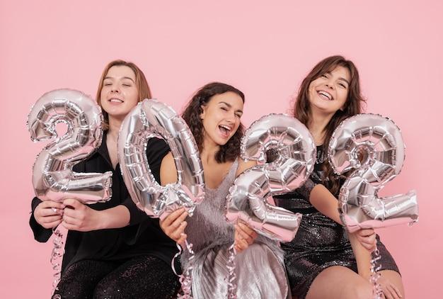 Een groep meisjes met zilveren folieballonnen in de vorm van de cijfers