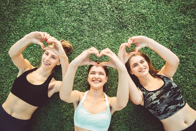 Een groep meisjes toont een hartgebaar met hun handen liggend op het gras