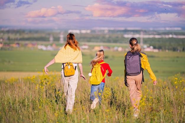 Een groep meisjes wandelend in de natuur, rennend naar de stad ver aan de horizon
