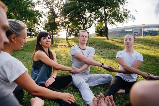 Een groep mensen doet yoga in een cirkel in de open lucht tijdens zonsondergang. gezonde levensstijl, meditatie en wellness.