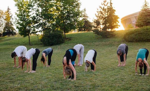 Een groep mensen doet yoga in het park bij zonsondergang. gezonde levensstijl, meditatie en wellness.