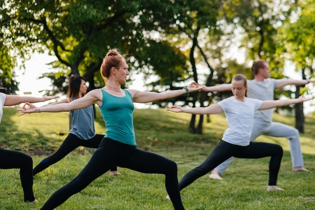 Een groep mensen doet yoga in het park bij zonsondergang