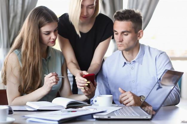 Een groep mensen in een café kijken naar smartphone app