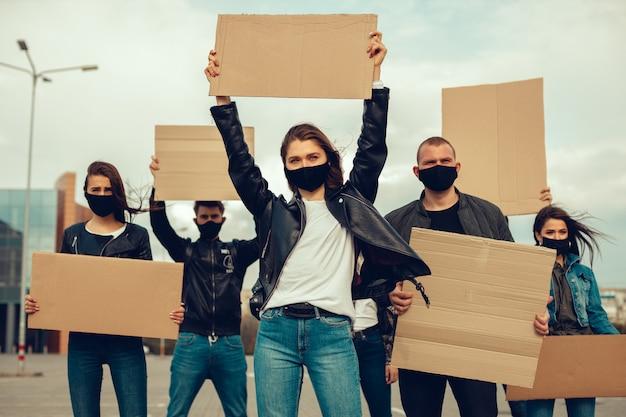 Een groep mensen met masker en posters om te protesteren het protest van de bevolking tegen het coronavirus