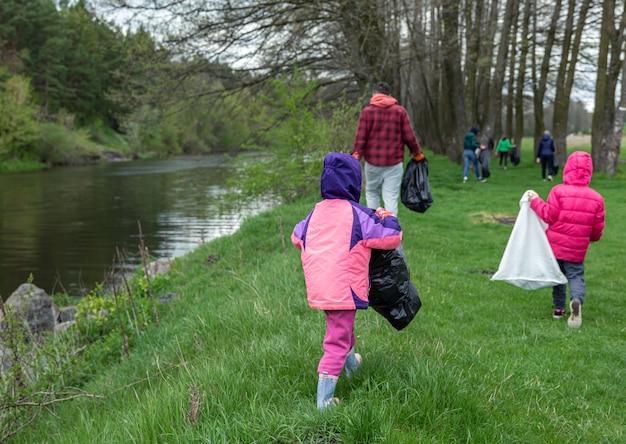 Een groep mensen ruimt in het voorjaar het afval op bij de uitgang naar het bos.
