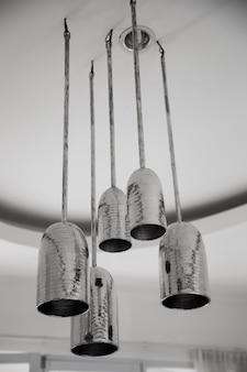 Een groep metaltische hangende lichten op wit plafond in loft ontworpen appartement.
