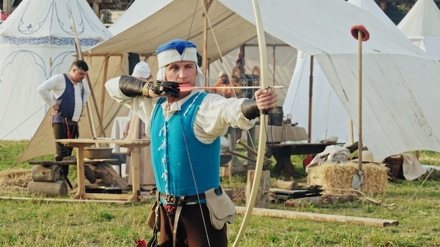 Een groep middeleeuwse boogschutters traint boogschieten. ridders kamp. historische reconstructie van de 14-15e eeuw, vlaanderen.