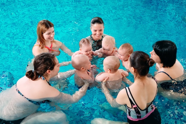 Een groep moeders met hun jonge kinderen in een kinderzwemles met een coach.