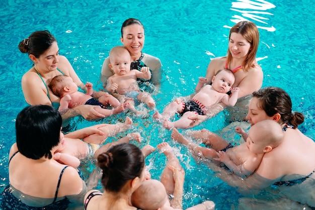 Een groep moeders met hun jonge kinderen in een zwemles voor kinderen met een coach.
