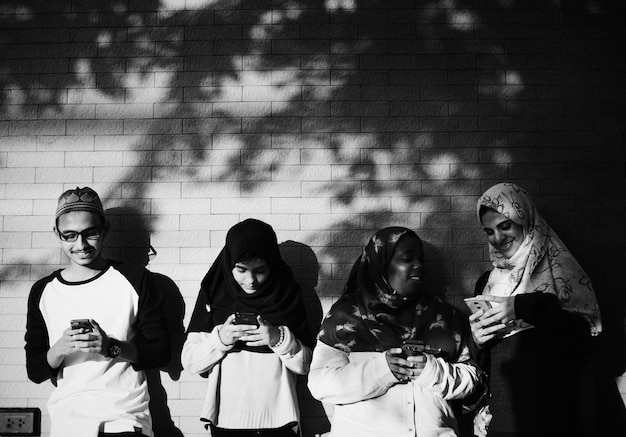 Een groep moslimstudenten die mobiele telefoons gebruiken