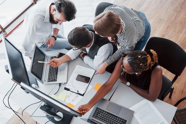 Een groep multinationale drukbezette mensen die op kantoor werken.
