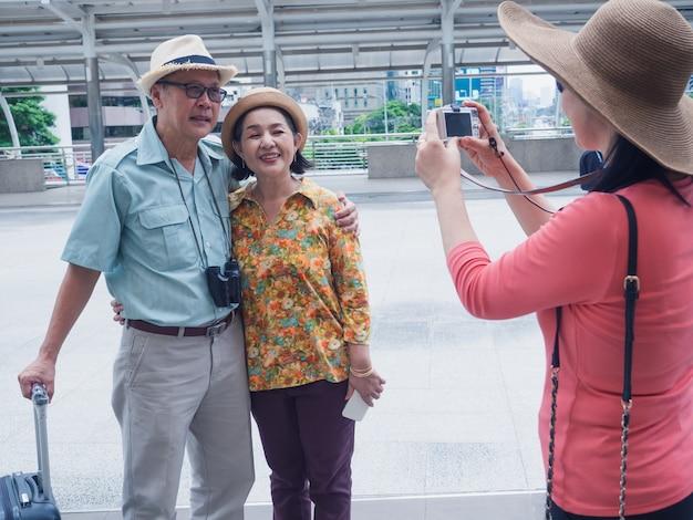 Een groep oudere mensen staan en foto's nemen tijdens het reizen in de stad
