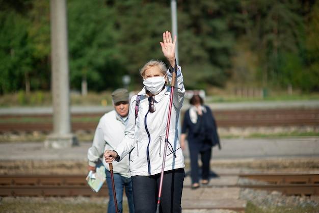 Een groep oudere reizigers met maskers op hun gezicht steekt het spoor over