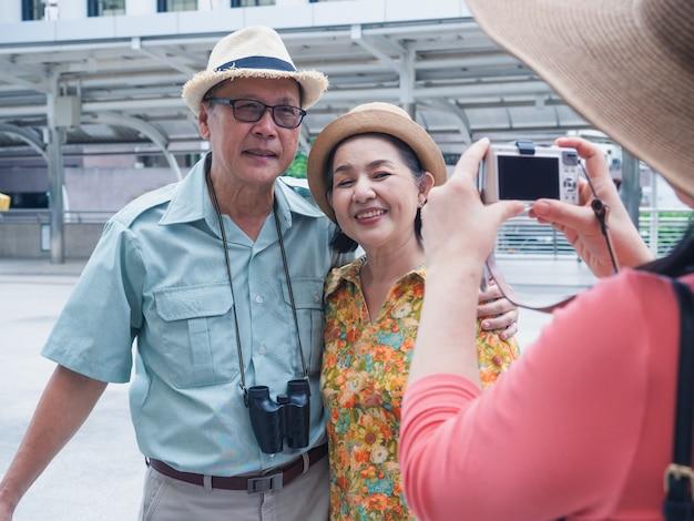 Een groep ouderen staan en foto's nemen tijdens het reizen in de stad