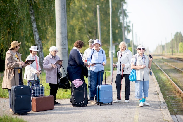 Een groep positieve oudere ouderen reizigers met behulp van tablets wachten op trein voordat ze op reis gaan