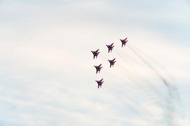 Een groep russische militaire vliegtuigen toont kunstvluchten in de blauwe lucht tegen de achtergrond van wolken.