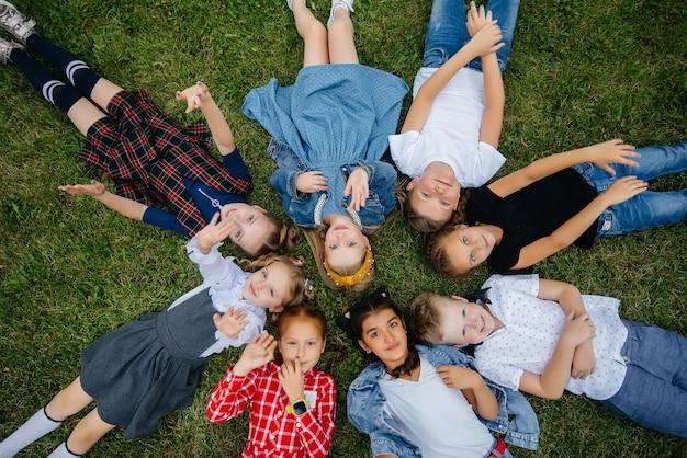 Een groep schoolkinderen ligt in een cirkel op het gras en heeft plezier