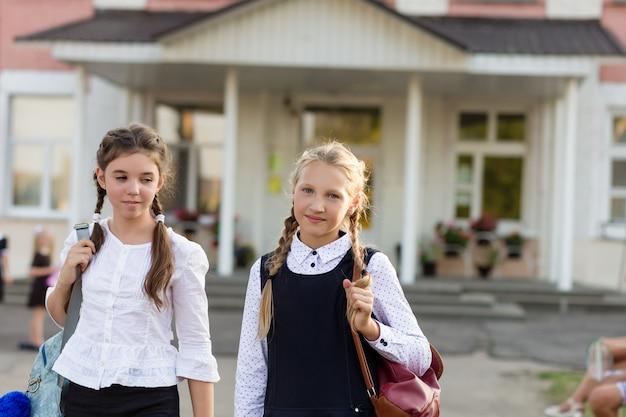 Een groep schoolmeisjes met rugzakken gaat naar school