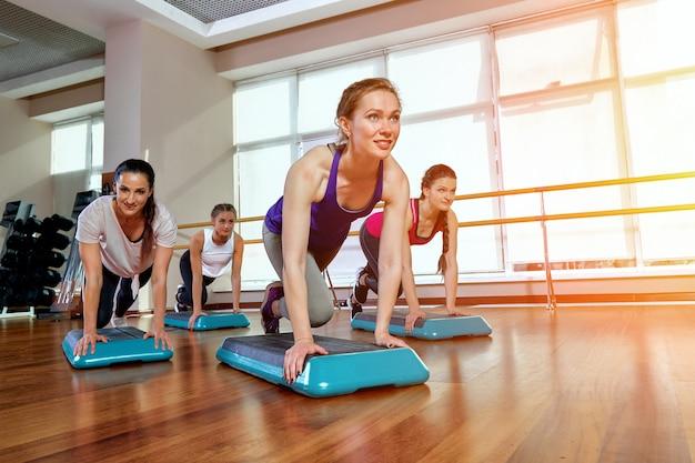 Een groep sportieve jongeren in sportkleding, in een fitnessruimte, push-ups doen of planken in de sportschool.