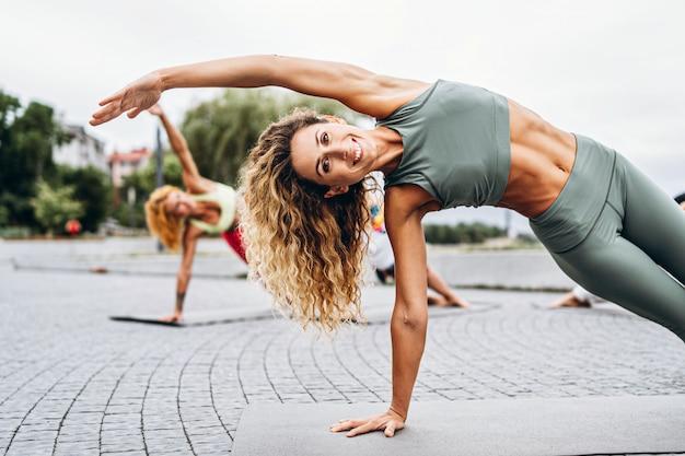 Een groep sportieve vrouwen oefent yogaoefeningen op de mat in het park met persoonlijke coach uit. actieve levensstijl.