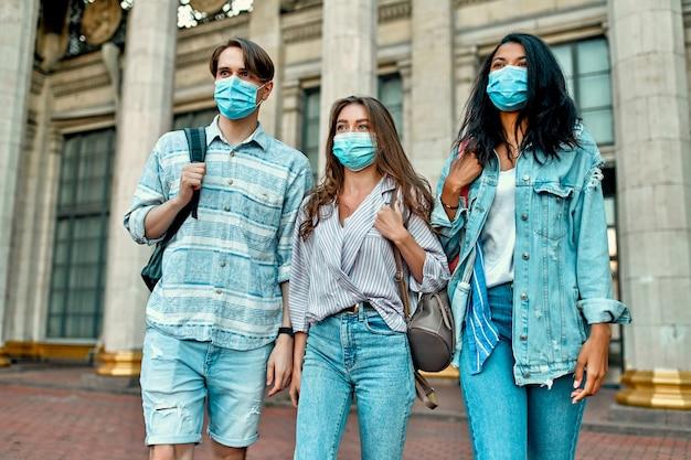 Een groep studenten die beschermende medische maskers dragen dichtbij de campus.