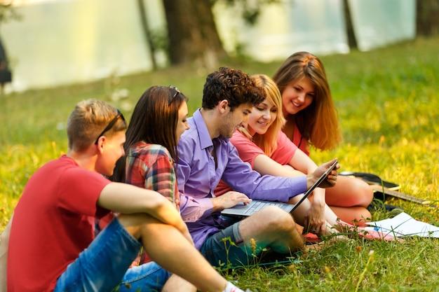 Een groep studenten die met laptop ontspannen in het park op een zonnige dag