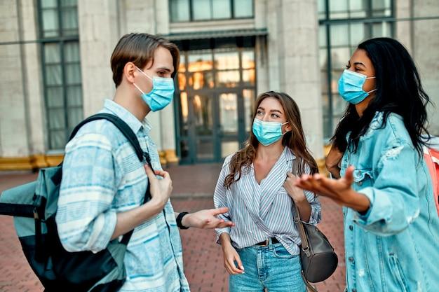 Een groep studenten met beschermende medische maskers praat buiten de campus.