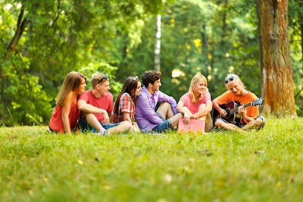 Een groep studenten met een gitaar die op een zonnige dag in het park rust