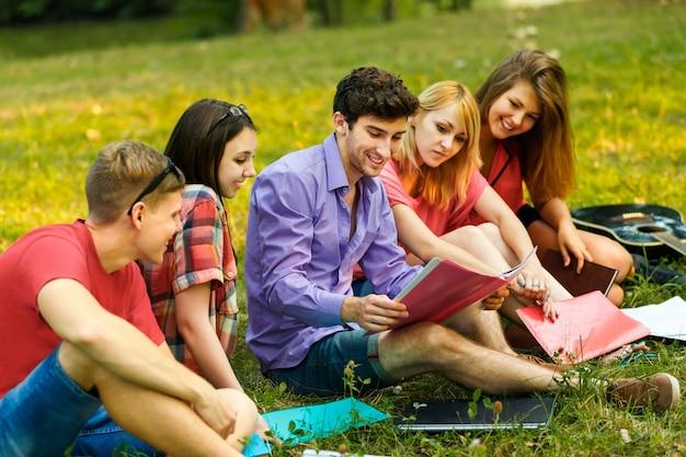 Een groep studenten met laptop ontspannen in het park op een zonnige dag