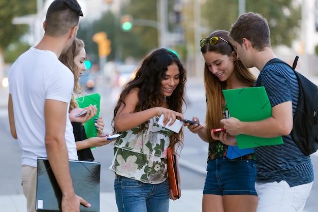 Een groep studenten met plezier met smartphones na de les.