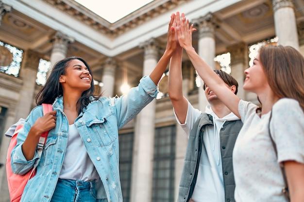 Een groep studenten slaagt voor het examen en toont de high-five in het overwinningsteken