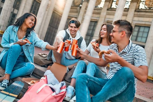 Een groep studenten zit op de trap buiten de campus en eet pizza en frisdrank. een groep vrienden ontspant en kletst.